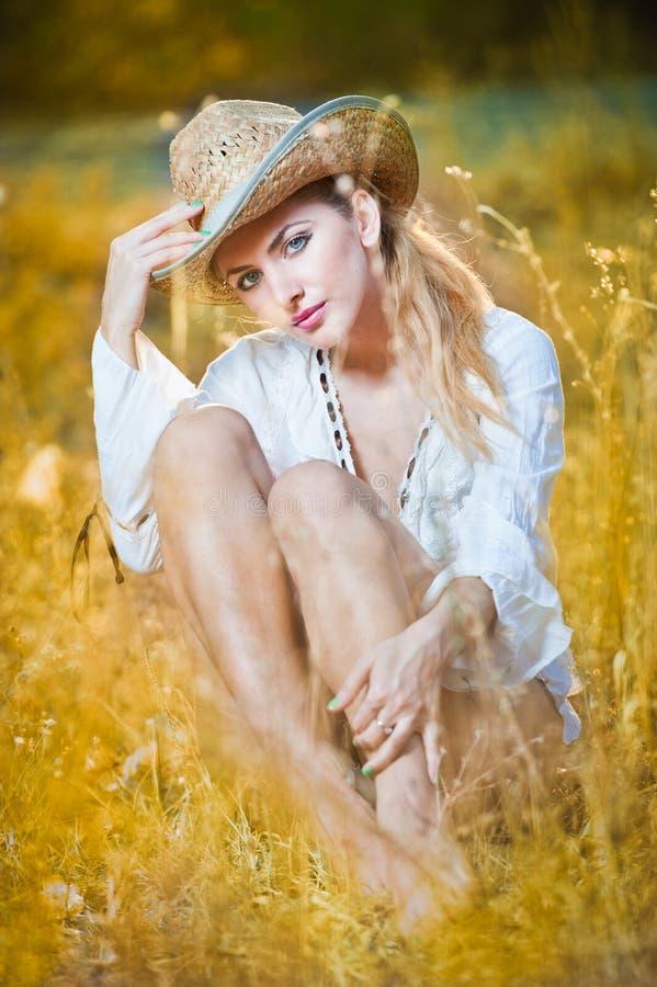 Façonnez la femme de portrait avec le chapeau et la chemise blanche se reposant sur une pile de foin photo stock