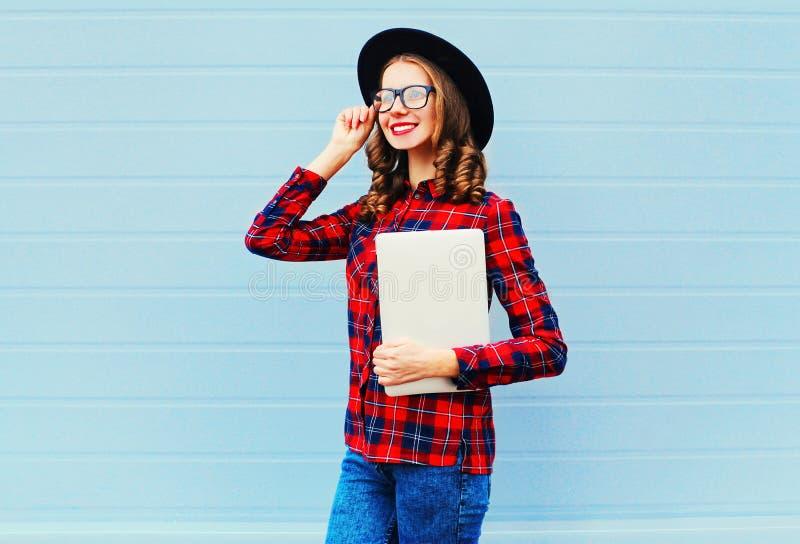 Façonnez la femme de sourire assez jeune tenant l'ordinateur portable ou le PC de comprimé dans la ville, le chapeau noir de port images stock