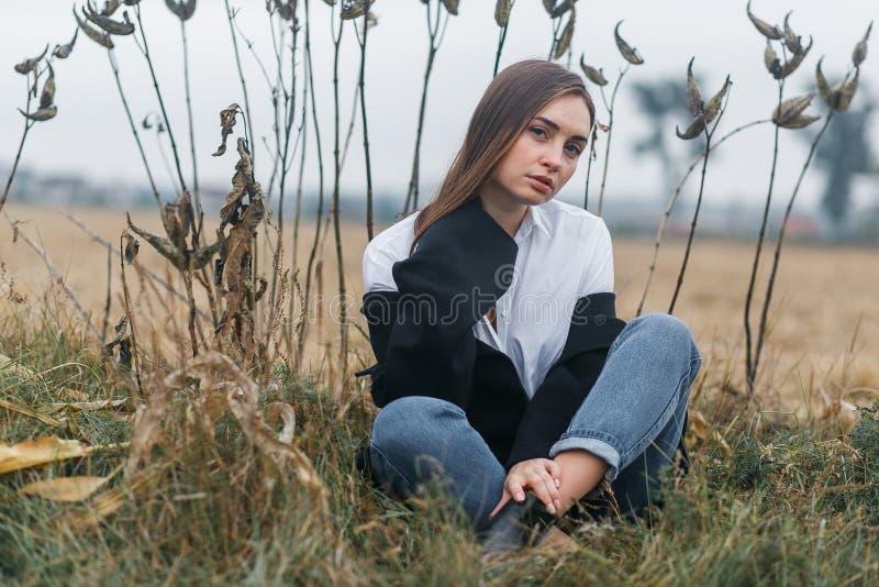 Façonnez la femme extérieure avec l'herbe peu commune sur le fond dans le domaine de paysage d'automne images stock