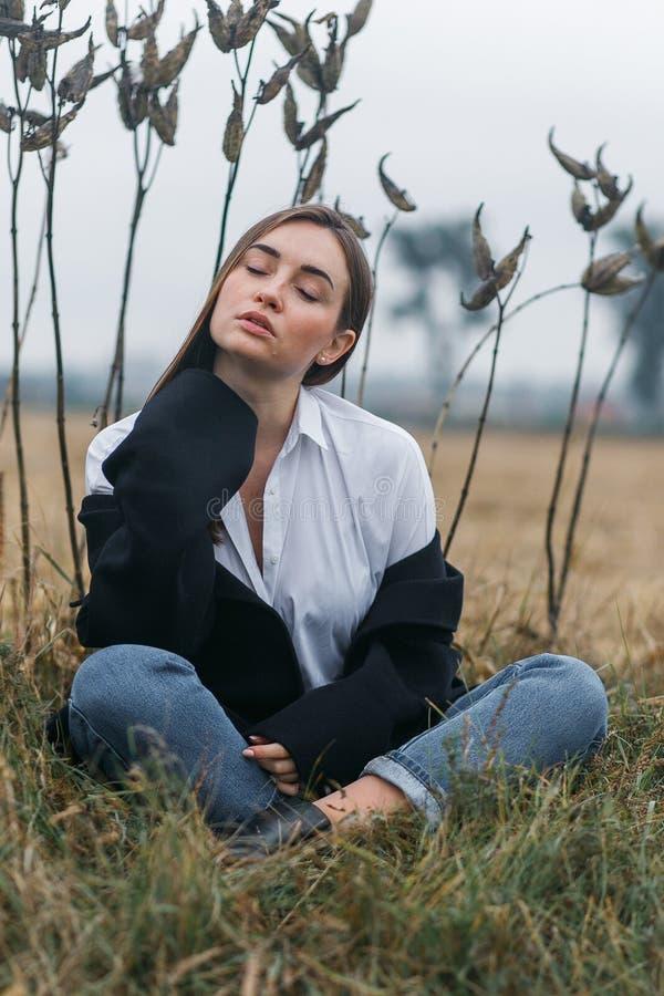 Façonnez la femme extérieure avec l'herbe peu commune sur le fond dans le domaine de paysage d'automne photographie stock