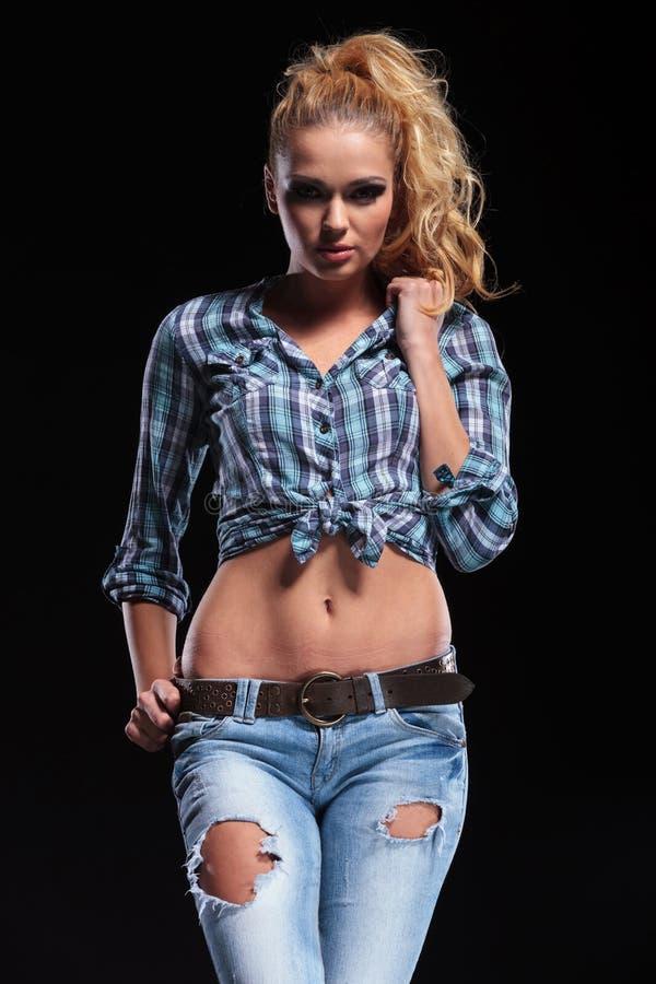 Façonnez la femme sexy dans les jeans et la chemise tenant son collier photos libres de droits
