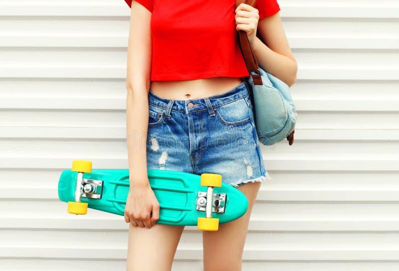 Façonnez la fille avec la planche à roulettes dans des shorts de denim au-dessus de blanc image libre de droits
