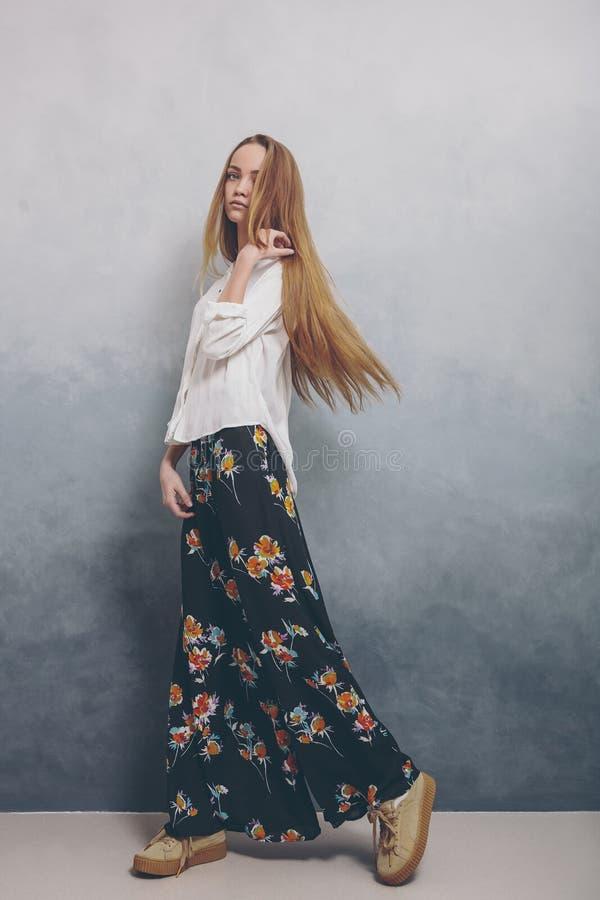 Façonnez la fille d'adolescent se tenant sur le plancher sur le fond grunge texturisé bleu de mur photo stock