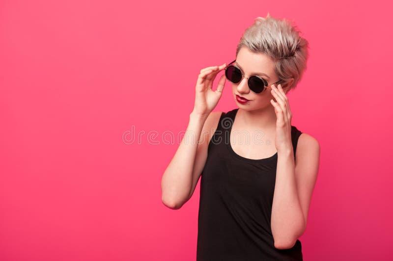 Façonnez la fille dans la chemise et des lunettes de soleil noires sur le fond rose images libres de droits