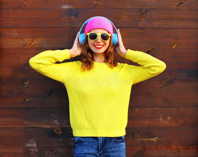 Façonnez la fille de sourire assez fraîche appréciant écouter la musique dans des écouteurs utilisant le chandail tricoté par jau photo stock