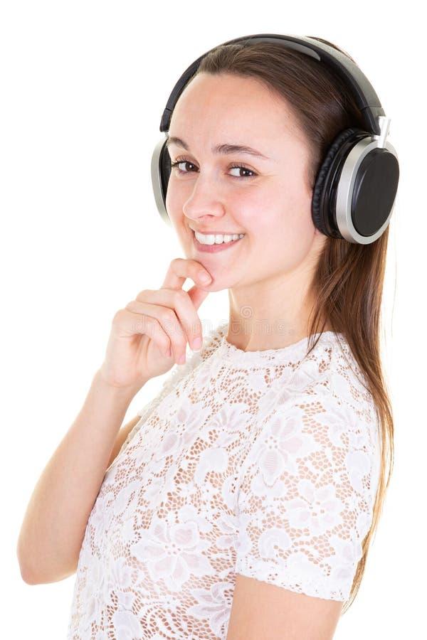 Façonnez la fille insouciante assez douce écoutant la musique dans des écouteurs photographie stock libre de droits