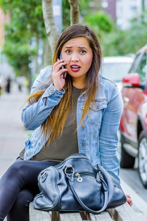Façonnez la jeune femme occasionnelle à la mode utilisant une veste de treillis et des guêtres noires, utilisant son téléphone po images stock