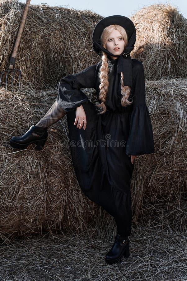 fa onnez la jeune femme utilisant la robe et le chapeau noirs l gants la campagne style amish. Black Bedroom Furniture Sets. Home Design Ideas