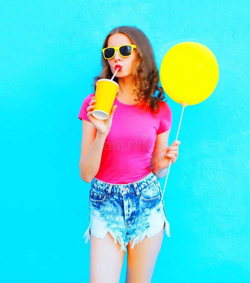 Façonnez la jeune femme utilisant un T-shirt, jus de fruit de boissons de shorts de denim de tasse avec le ballon à air jaune au- images libres de droits