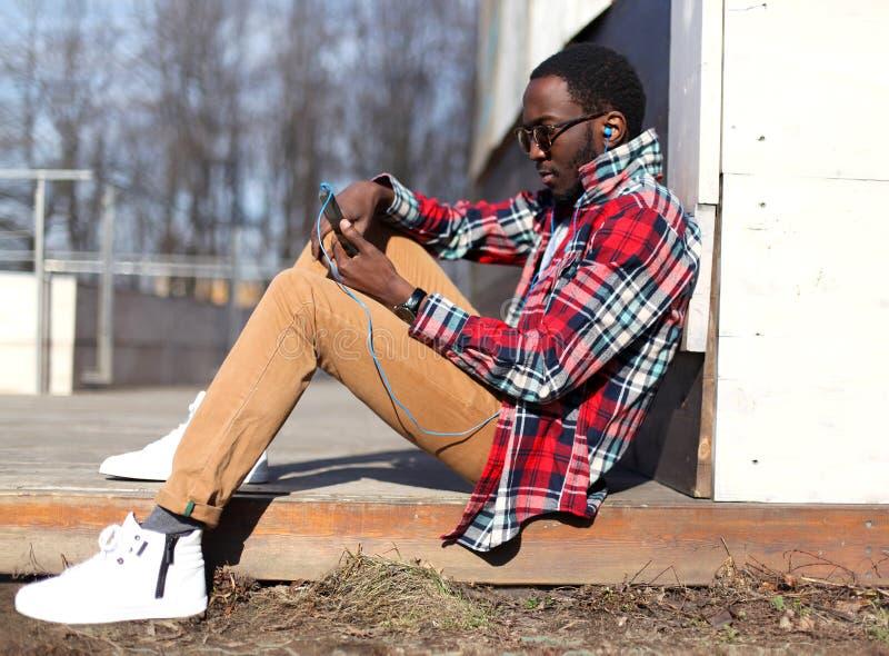 Façonnez la jeune séance africaine d'homme, utilisant le smartphone écoute la musique photos libres de droits