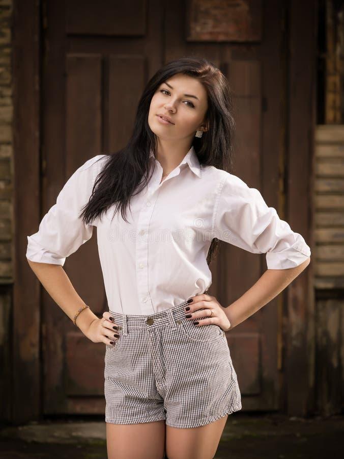 Façonnez la jolie pose de jeune femme extérieure près d'un vieux mur en bois photographie stock libre de droits