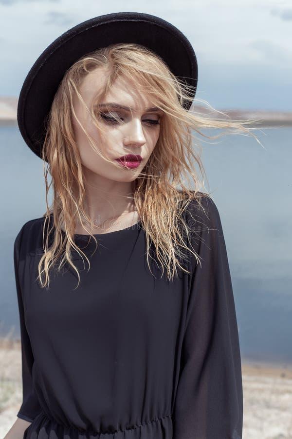 Façonnez la photo de la jeune belle fille sexy avec les cheveux humides dans un chapeau noir et une robe noire de coton avec le b photographie stock