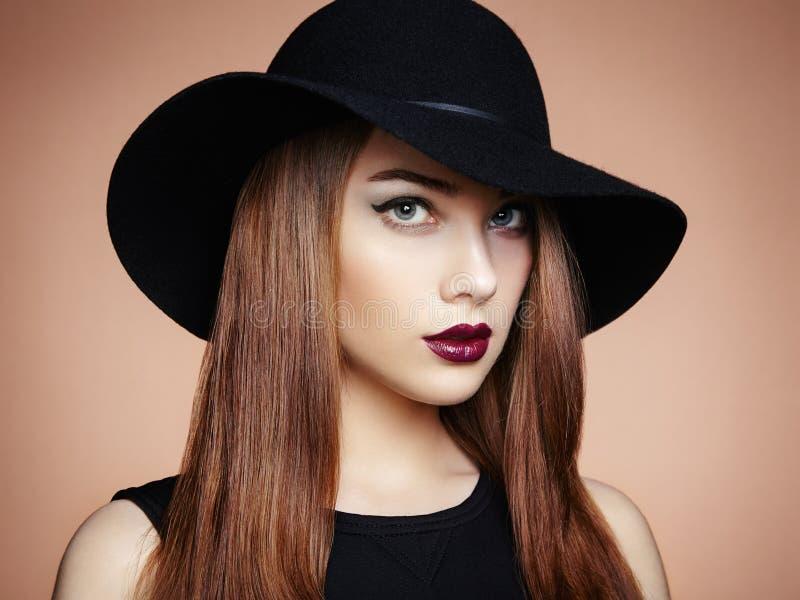 Façonnez la photo de la jeune femme magnifique dans le chapeau Pose de fille photos stock