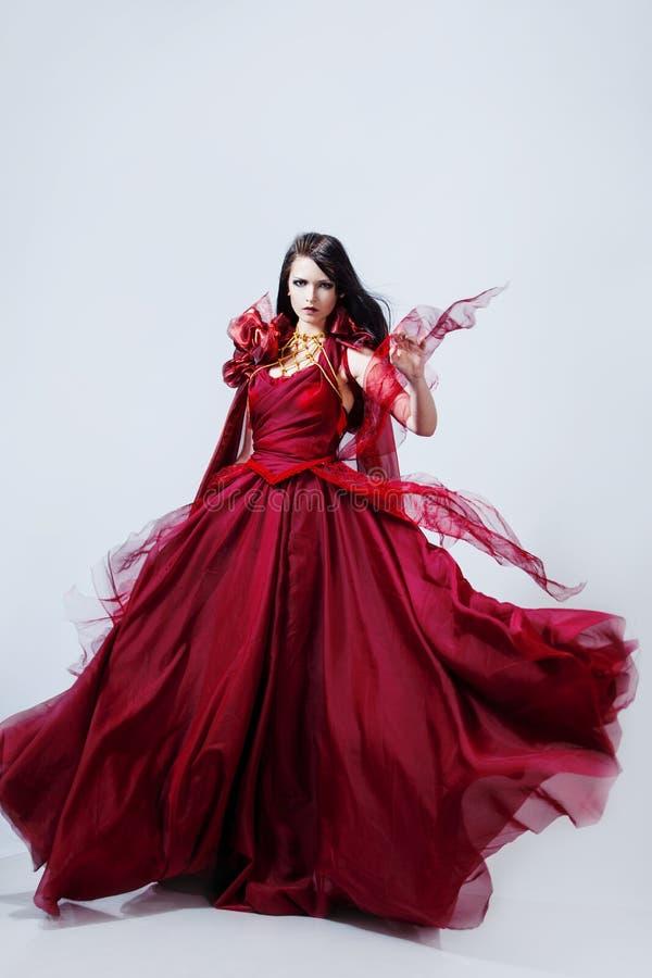 Façonnez la photo de la jeune femme magnifique en rouge image stock