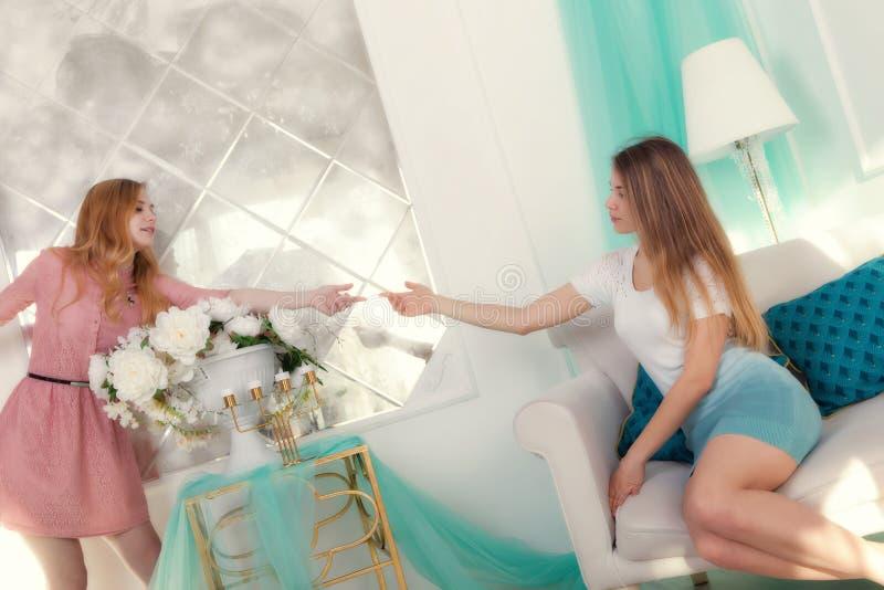 Façonnez la photo intérieure de deux belles jeunes filles avec la lumière h image stock