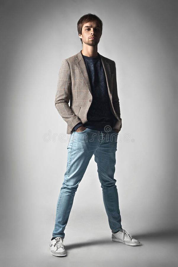 Façonnez la pose occasionnelle habillée par modèle d'homme dramatique dans le studio images stock