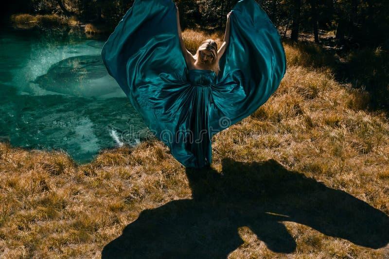 Façonnez la pousse de la femme dans la longue robe bleue près du lac photographie stock