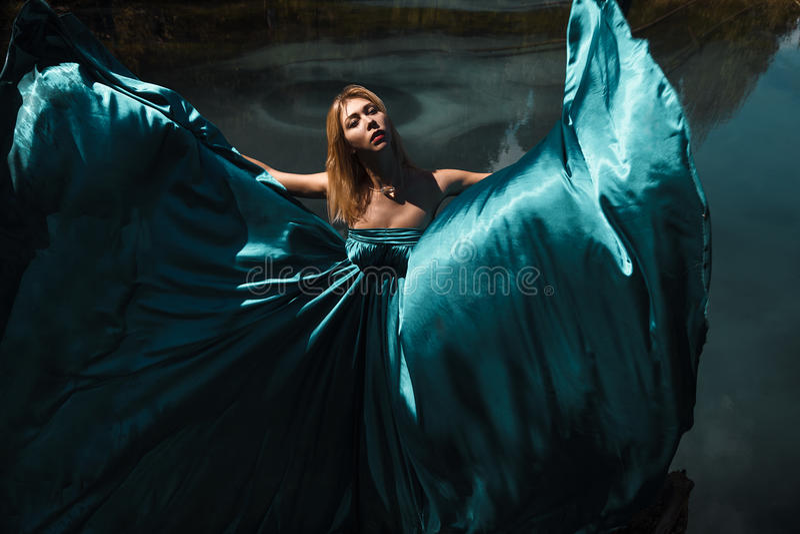 Façonnez la pousse de la femme dans la longue robe bleue près du lac image libre de droits