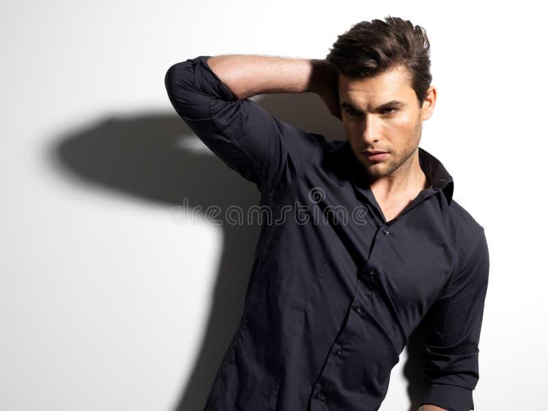Façonnez la verticale de l'jeune homme dans la chemise noire photographie stock