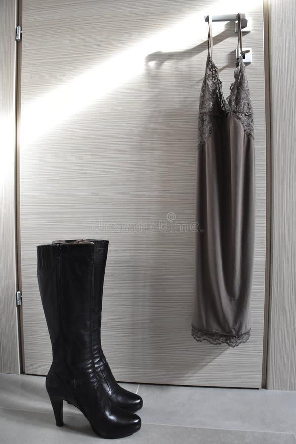 Façonnez le babydoll et les bottes sur une porte ensoleillée photo libre de droits