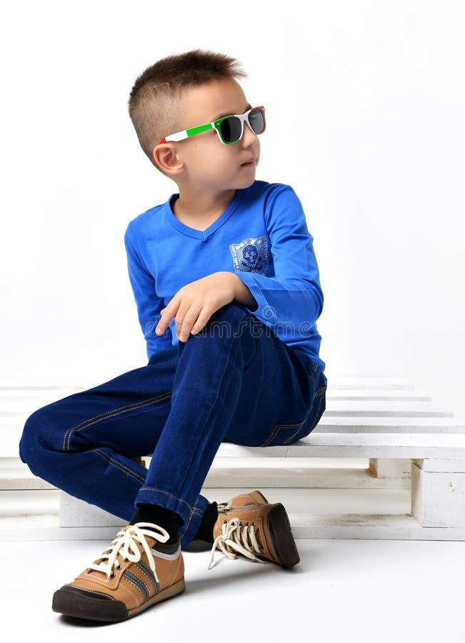 Façonnez le beau petit garçon en treillis bleu de tissu de lunettes de soleil de l'Italie image libre de droits
