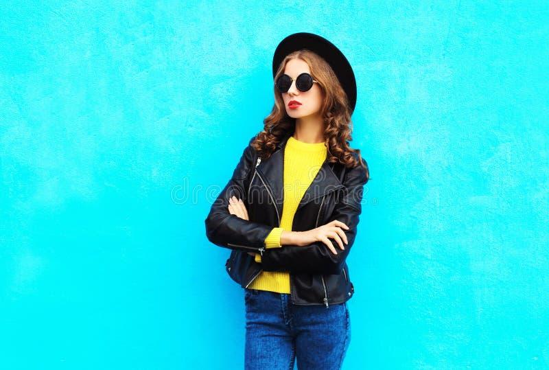 Façonnez le joli modèle de femme dans des vêtements noirs de style de roche au-dessus de bleu coloré photo libre de droits