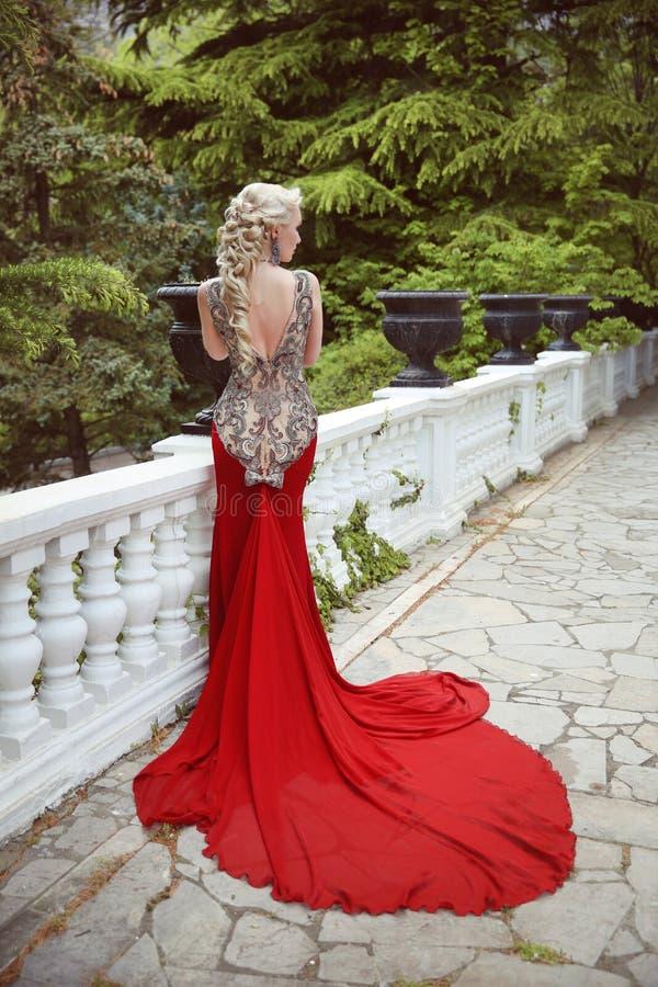 Façonnez le modèle blond élégant de femme dans la robe rouge avec le long train de photos stock