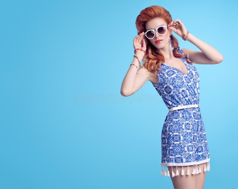 Façonnez le modèle roux dans la salopette d'été sur le bleu photo libre de droits