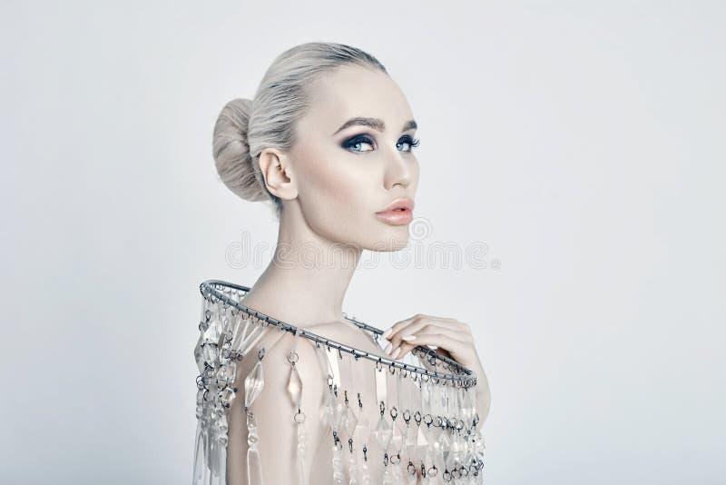 Façonnez le portrait d'art d'une blonde avec un grand collier brillant, une femme nue, des soins de la peau, un visage et un corp image stock