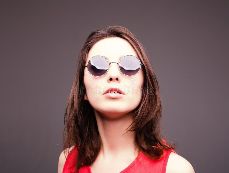 Façonnez le portrait d'une belle femme de brune en verres photo stock