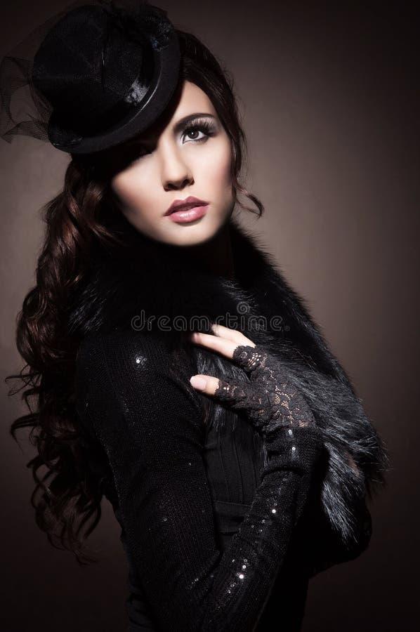 Façonnez le portrait d'une femme de brune dans des vêtements noirs photo stock