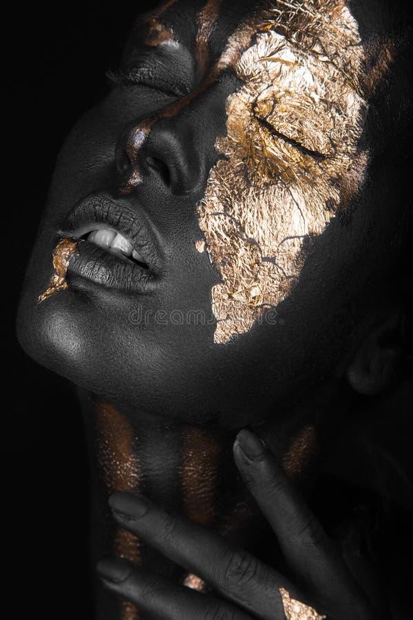 Façonnez le portrait d'une fille à la peau foncée avec le maquillage d'or Visage de beauté photos stock