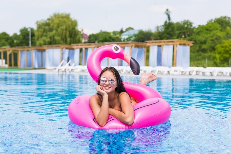 Façonnez le portrait d'une jeune et sexy fille dans la piscine sur un flamant rose gonflable dans un maillot de bain et des lunet photo stock
