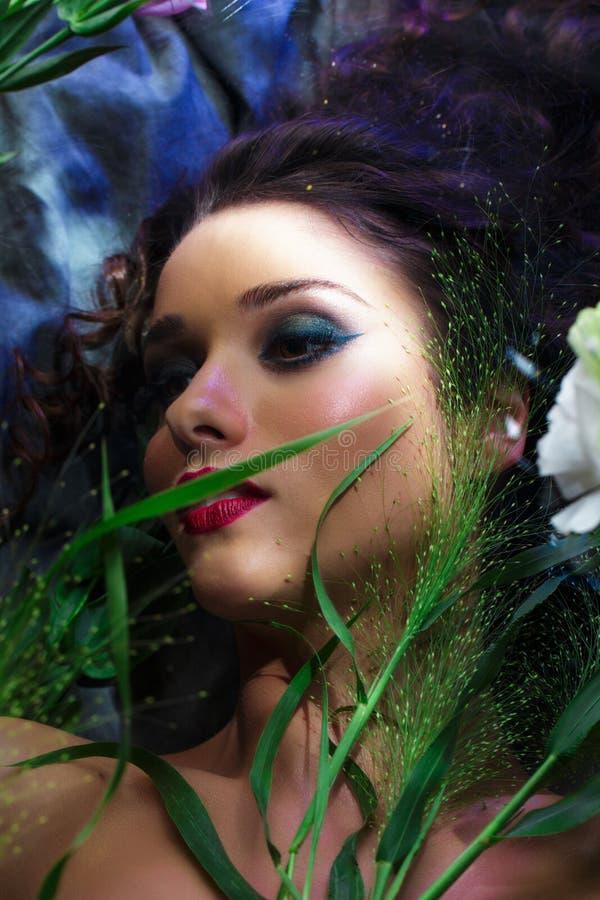 Façonnez le portrait de la belle fille avec lumineux composent parmi des eustomas images stock