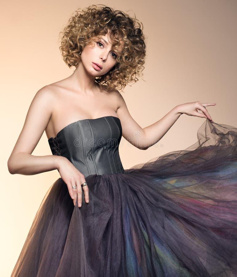 Façonnez le portrait de la belle jeune femme dans une robe grise Coiffure volumineuse photos libres de droits