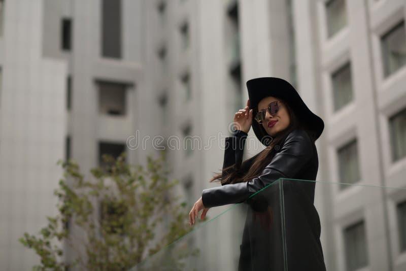 Façonnez le portrait de la femme attirante dans le chapeau noir au loin débordé a photo stock