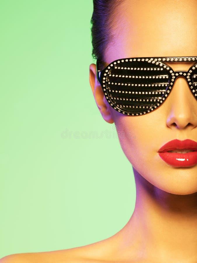 Façonnez le portrait de la femme utilisant les lunettes de soleil noires avec des strass photo stock