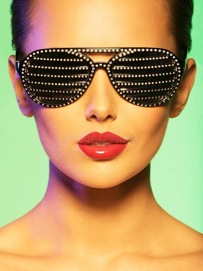Façonnez le portrait de la femme utilisant les lunettes de soleil noires avec le diamant images stock