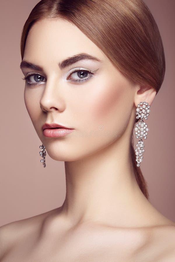 Façonnez le portrait de la jeune belle femme avec des bijoux photo stock