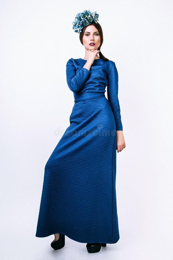 Façonnez le portrait de la jeune belle fille dans la longue robe bleue Fond blanc photo stock