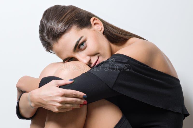 Façonnez le portrait de la jeune femme de beauté s'asseyant sur le fond blanc image libre de droits