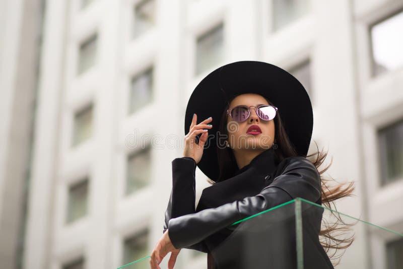 Façonnez le portrait de la jolie femme dans le chapeau noir au loin débordé et le m photos stock