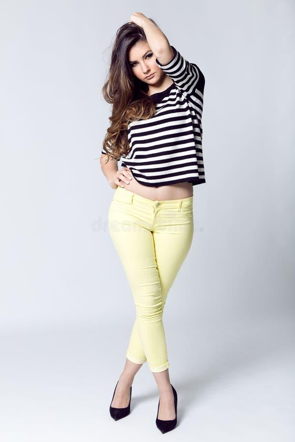 Façonnez le portrait de la jolie jeune femme posant dans le phot de studio photo stock