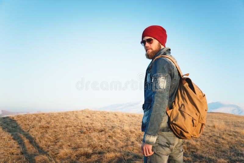 Façonnez le portrait des lunettes de soleil de port d'un jeune homme barbu de hippie, d'un sac à dos et du chapeau sur un fond av photographie stock