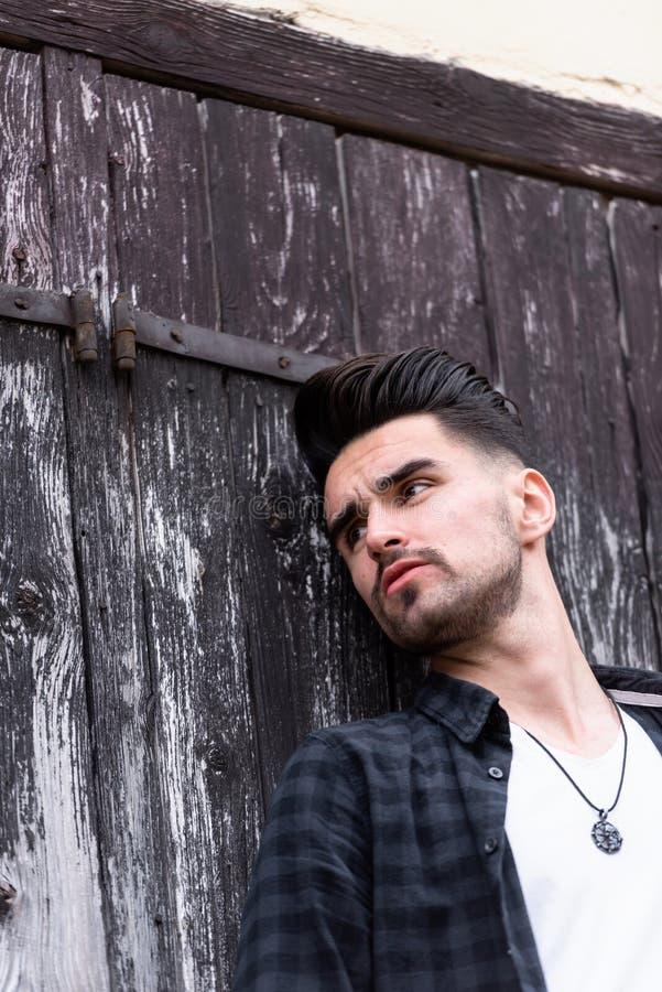 Façonnez le portrait du jeune homme beau sur le fond rustique en bois photographie stock libre de droits