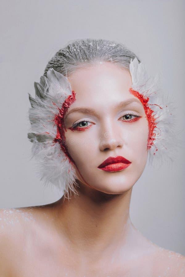 Façonnez le portrait en gros plan d'une fille modèle dans l'image d'un cygne avec un maquillage étonnant de beauté photos stock