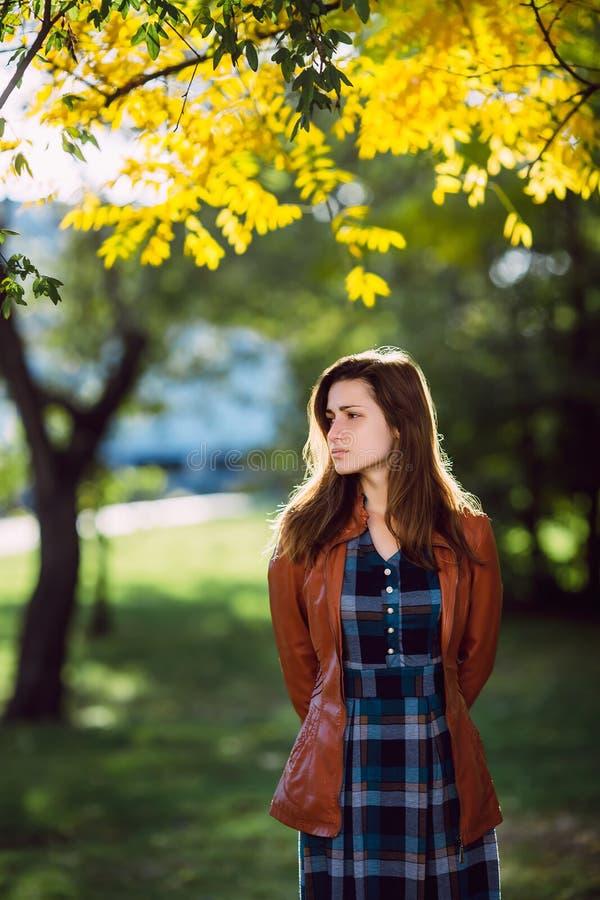 Façonnez le portrait extérieur de la femme magnifique de cheveux foncés dans la robe à carreaux élégante et la veste en cuir brun images libres de droits