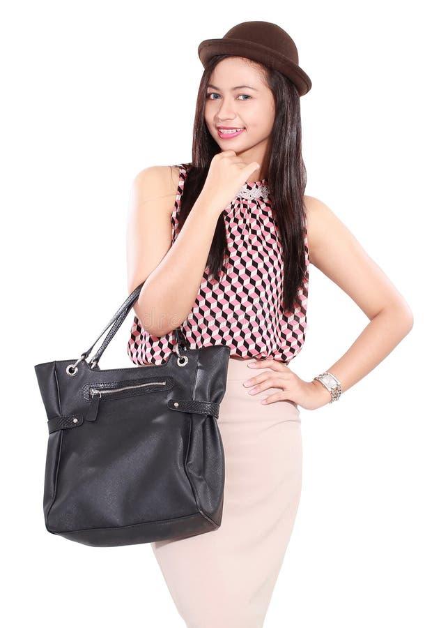 Façonnez le rétro portrait de la jeune femme élégante avec le sac en cuir image libre de droits