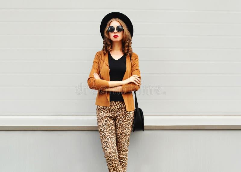 Façonnez le regard, la jolie jeune femme utilisant un rétro chapeau élégant, les lunettes de soleil, la veste brune et l'embrayag photographie stock