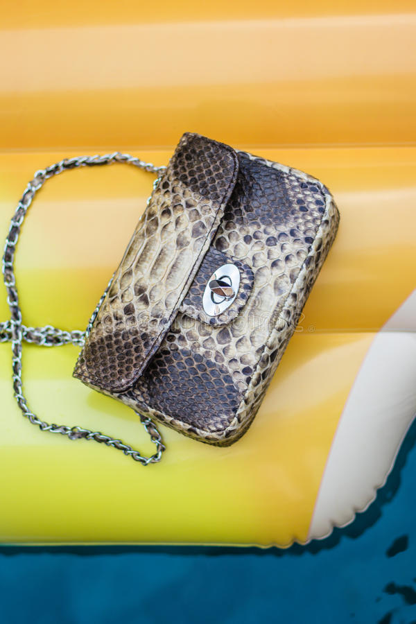 Façonnez le sac à main de luxe de python de peau de serpent sur un matelas jaune gonflable dans la piscine Humeur d'été images stock